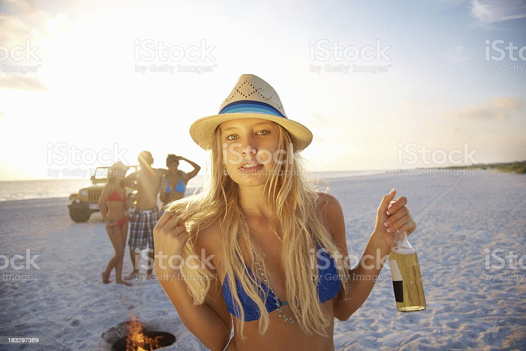 Girl holding beer bottle with friends in background on beach royalty-free stock photo