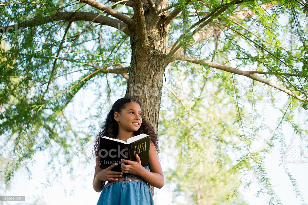 Girl holding Bible and looking away stock photo