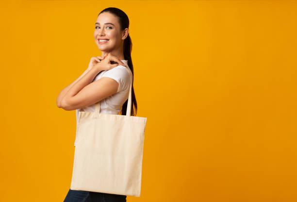 mädchen hält leere weiße eco-tasche auf gelbem hintergrund - kinderhandtaschen stock-fotos und bilder