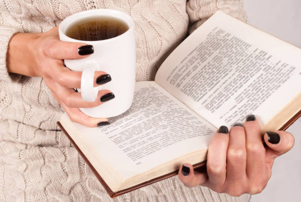 mädchen, buch und eine tasse tee in den händen halten und lesen - herbst nagellack stock-fotos und bilder