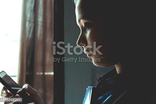 Indian teenager using smart phone at home indoor shoot and side view