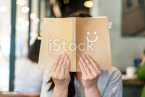 istock girl holding book covering face 692479464