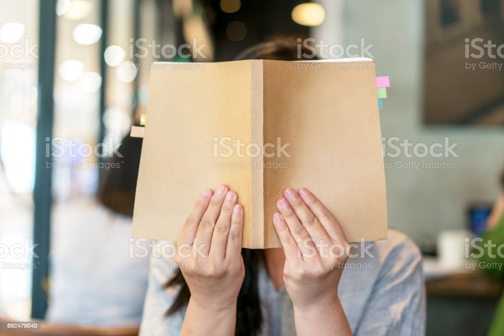 girl holding book covering face stock photo