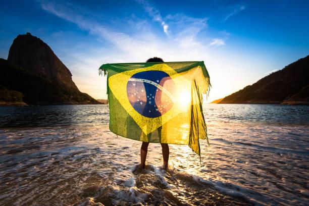 Girl Holding Brazilian Flag at the Beach stock photo