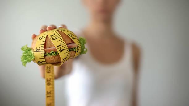 mädchen hält burger gefesselt mit klebeband, junk-food, ungesunde lebensweise zu messen - gewicht schnell verlieren stock-fotos und bilder
