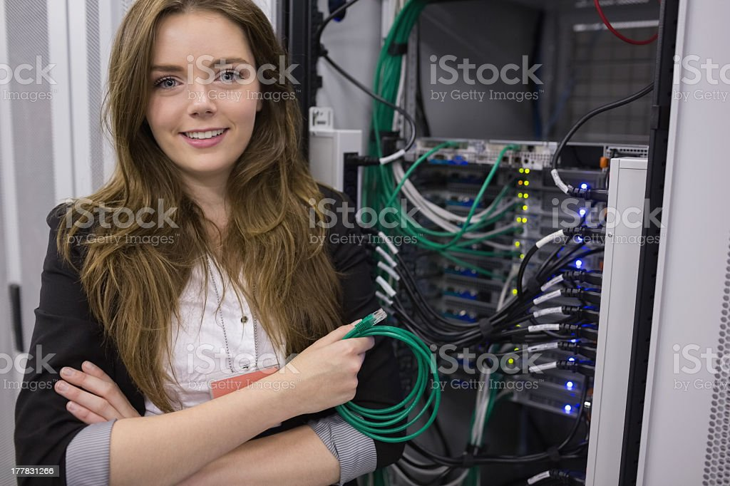 Girl holding cable in front of rack mounted servers stock photo