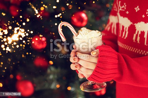 istock Girl holding cacao with whipped cream and peppermint candy cane. Christmas holiday concept. Holiday background. Festive holiday celebration bokeh 1163428649