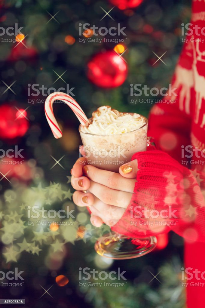 Girl holding cacao with whipped cream and peppermint candy cane. Christmas holiday concept. Holiday background stock photo