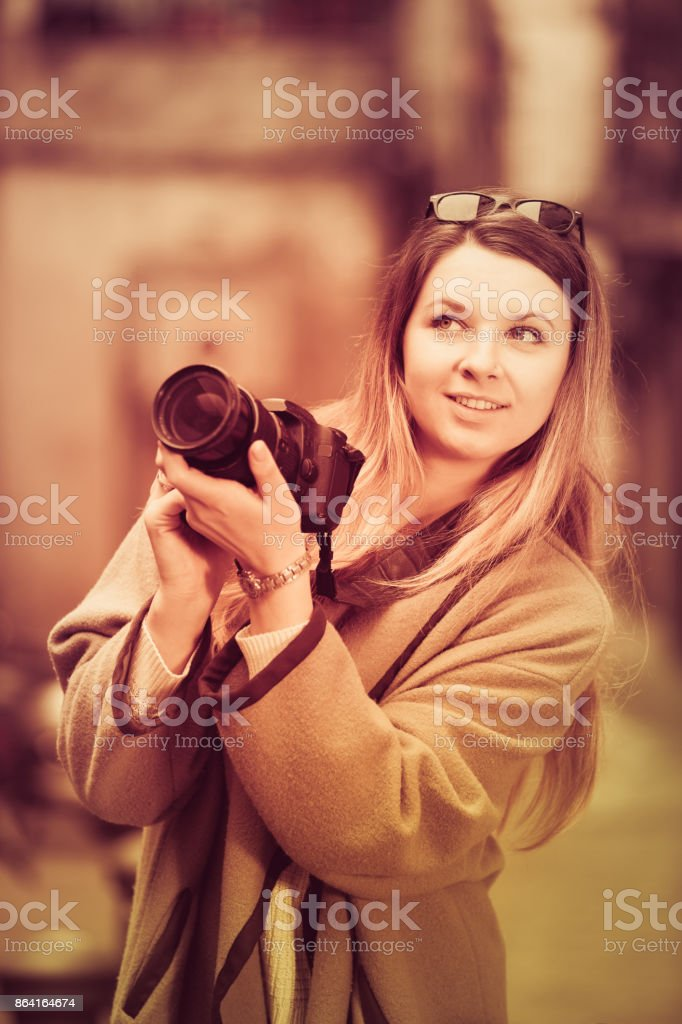 Girl holding camera and photographing royalty-free stock photo