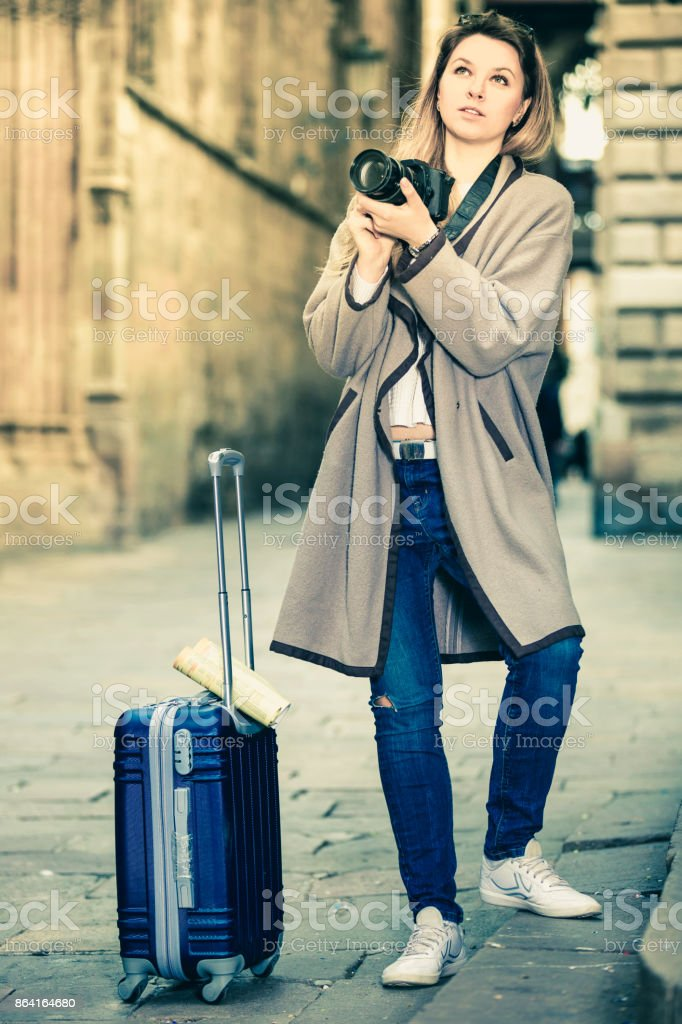 Girl holding camera in hands and photographing in the city royalty-free stock photo