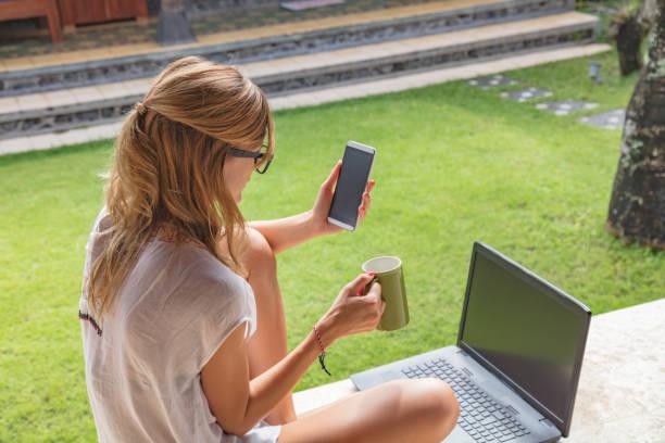mädchen mit handy, kaffee becher mit laptop auf einer veranda garten. - garden types stock-fotos und bilder