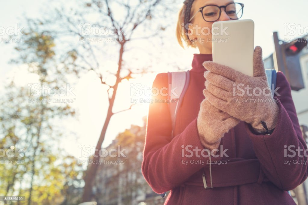 Girl holding cellphone in urban surroundings and crossing the street - danger! stock photo