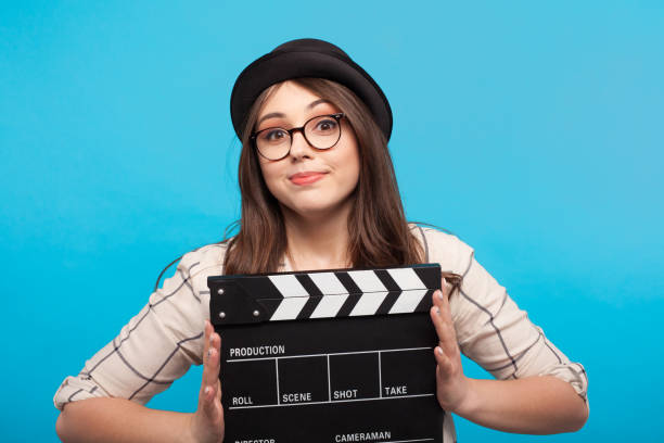 girl holding clapperboard - film director stock pictures, royalty-free photos & images