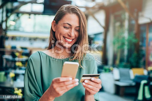 Young woman sitting in a cafe and holding credit card and smart phone