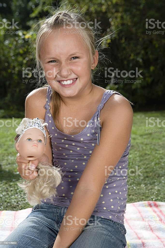 Girl holding dolls head royalty-free stock photo
