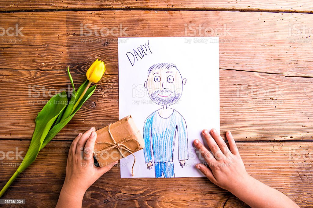 Girl holding drawing of her father and little gift. stock photo
