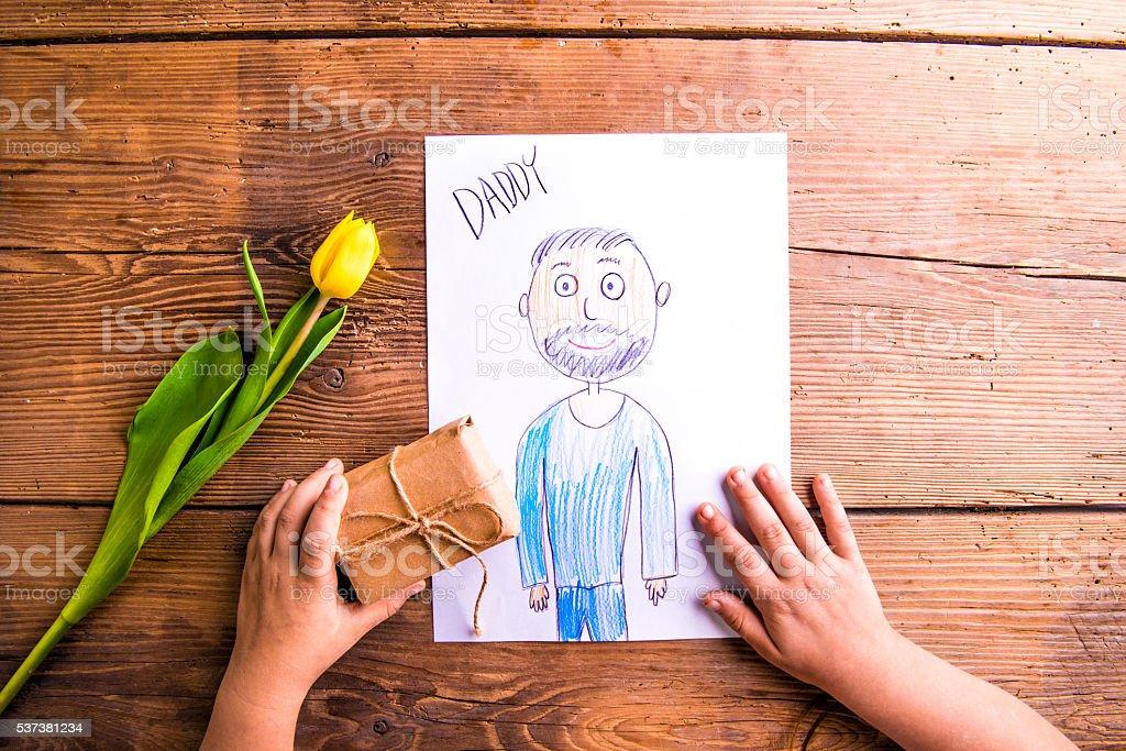 Menina segurando o desenho do seu pai e pouco de presente. - foto de acervo