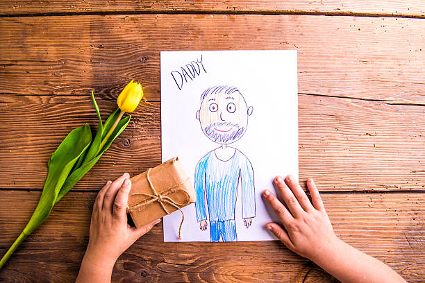 girl holding drawing of her father and little gift. - fathers day stock photos and pictures