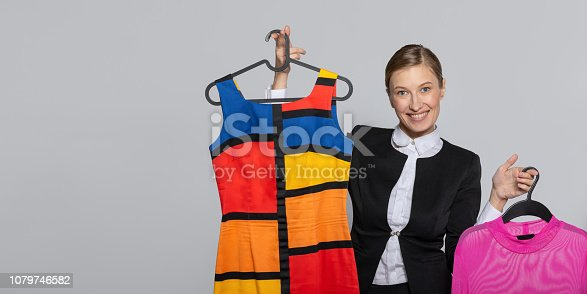 672064598istockphoto girl holding dresses in her hands 1079746582