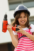Portrait of little girl dressed as engineer holding drill machine at construction site. Vertical shot.