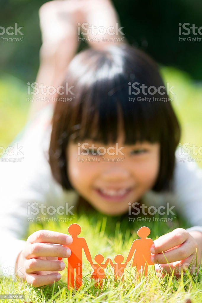 Girl Holding Family Paper Cut Out in Nature stock photo