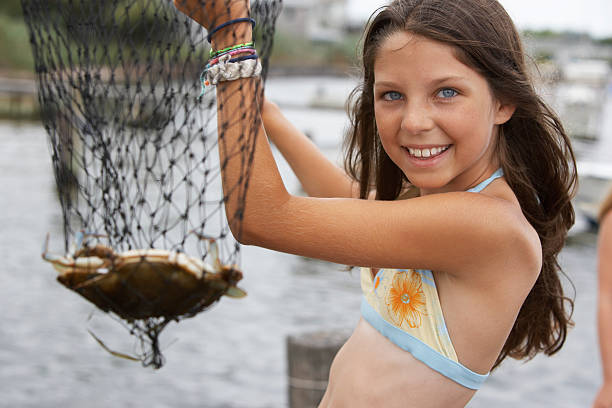 Girl (10-12) holding fishing net containing crab, close-up, portrait stock photo