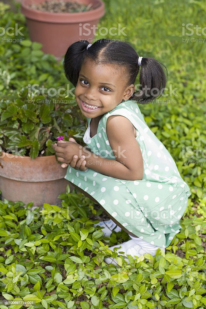 Girl (4-5) holding flower, smiling, portrait royalty-free stock photo