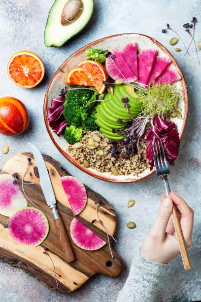 Mädchen hält Gabel und essen vegan, entgiftet Buddha-Schale mit Quinoa, Mikrogrün, Avocado, Blut Orange, Brokkoli, Wassermelone Radieschen, Alfalfa-Samen Sprossen. – Foto