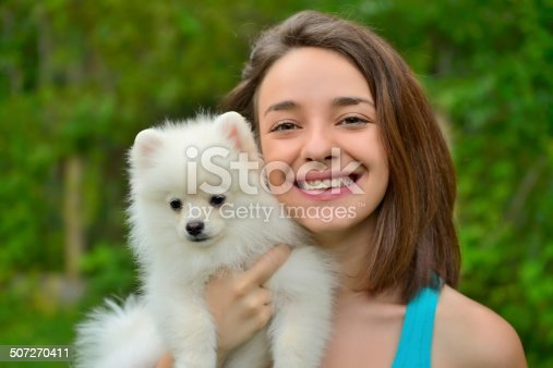 istock Girl holding german spitz puppy outside and smiling at camera. 507270411