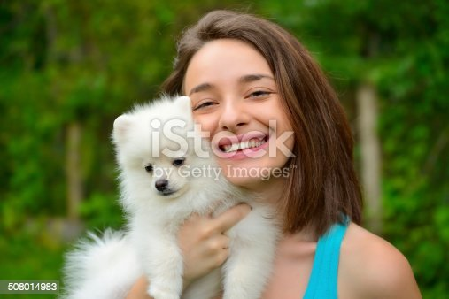 istock Girl holding german spitz puppy outside and smiling at camera. 508014983