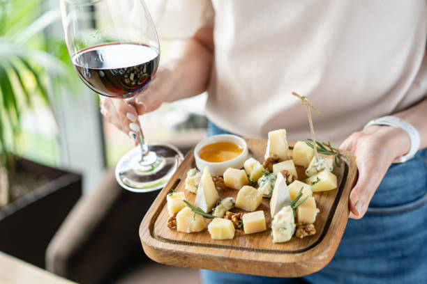 Girl holding glass red wine and wooden plate with cheese. Delicious cheese mix with walnuts, honey. Tasting dish on a wooden plate. Food for wine. stock photo
