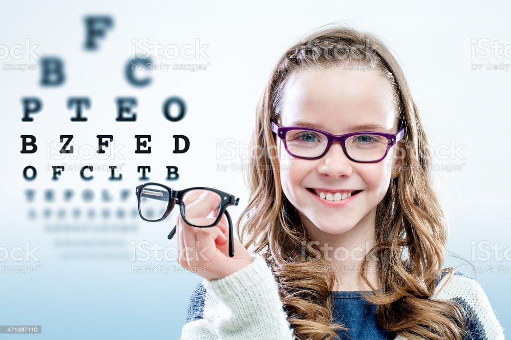 Mädchen mit Brille bei test-chart im Hintergrund. – Foto