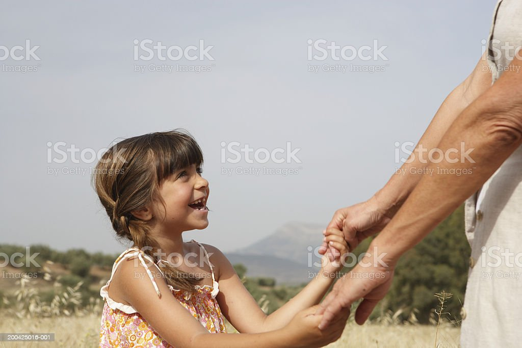 Girl (4-6) holding grandmother's hands, side view, close-up royalty-free stock photo