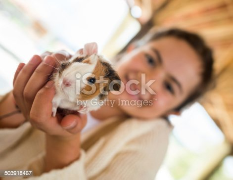 Happy girl holding cute guinea pig