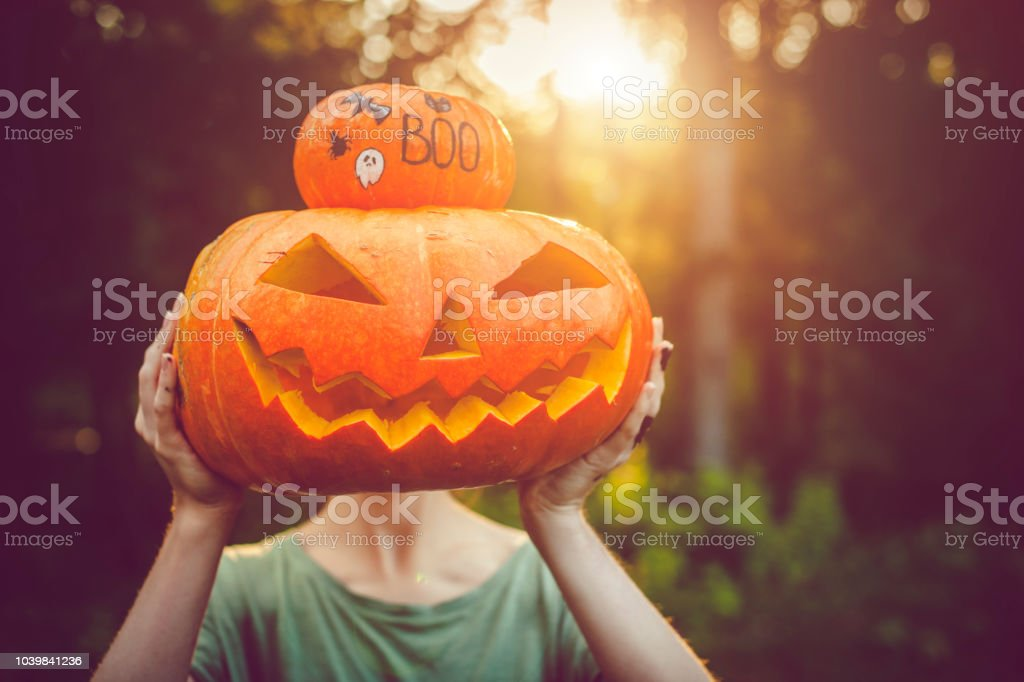Girl holding Halloween pumpkin and jack o' lantern stock photo