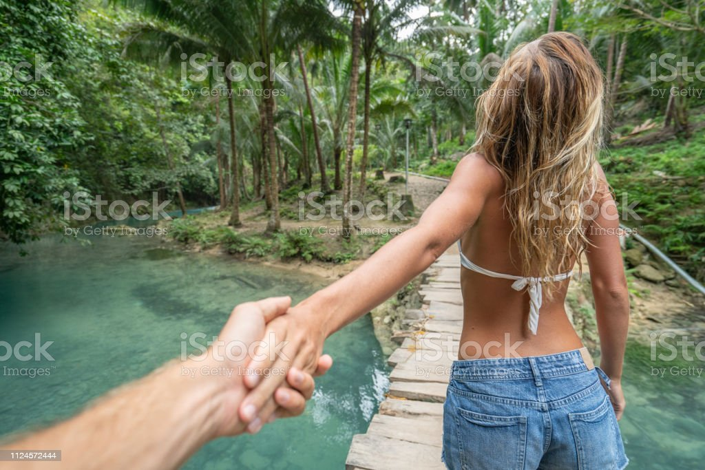 Follow me to concept young woman leading boyfriend to lush green...