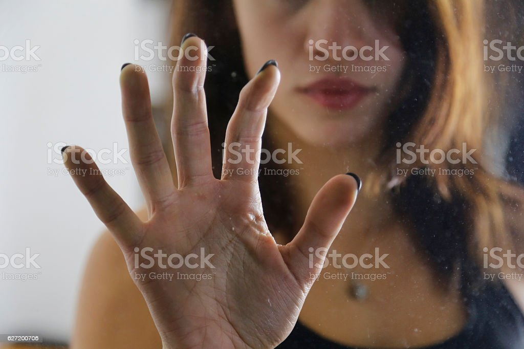 Girl holding hand on door glass stock photo