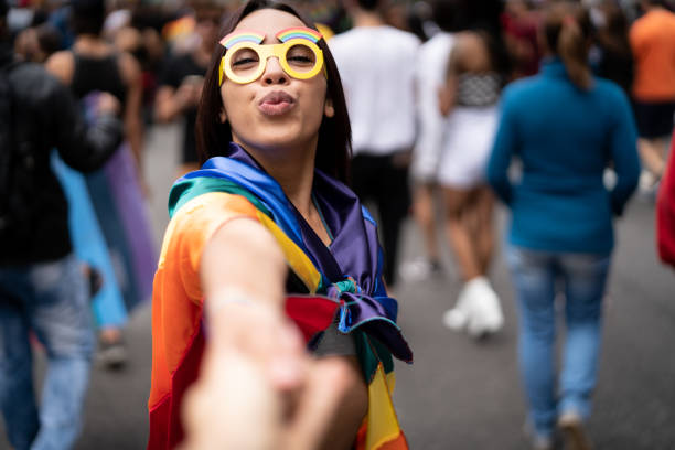 Girl Holding Hands and Following Boyfriend on Street Party Romantic Scene gay pride parade stock pictures, royalty-free photos & images
