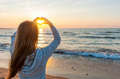 istock Girl holding hands in heart shape at beach 452578537