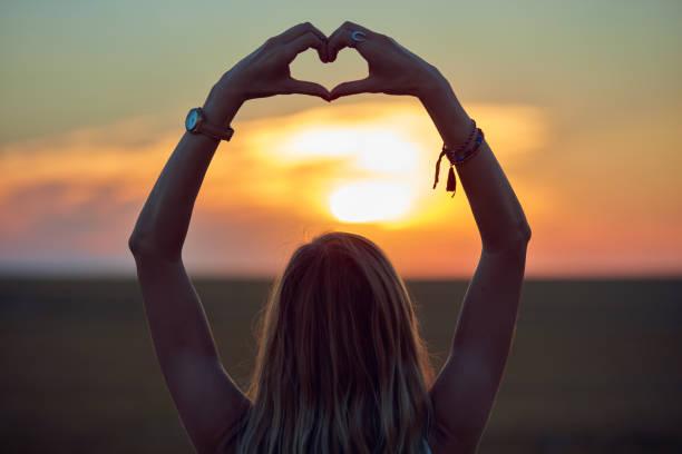 Girl holding heart-shape symbol for love in sunset / sunrise time. stock photo