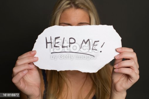 istock girl holding help me sign 161816972