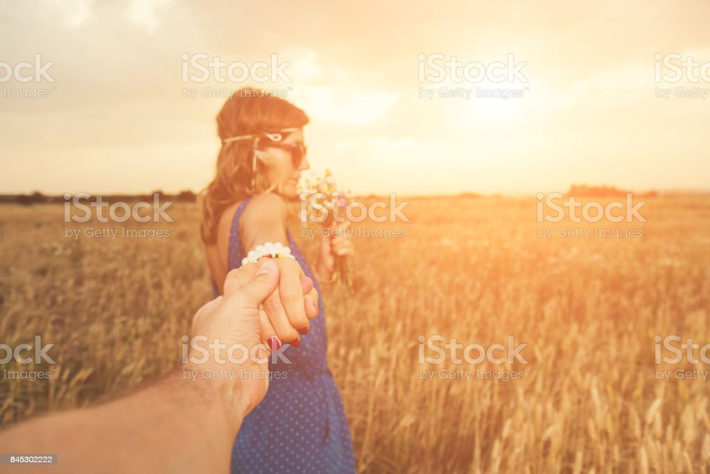 Girl holding her boyfrined in nature - wheat field. Focus is on the hands. stock photo