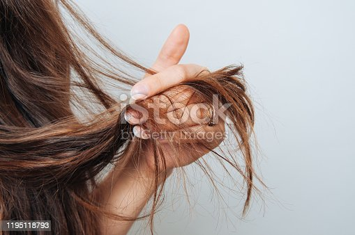 Girl holding her hair in her hand. Hair care concept. Shampoo. Haircut needed.