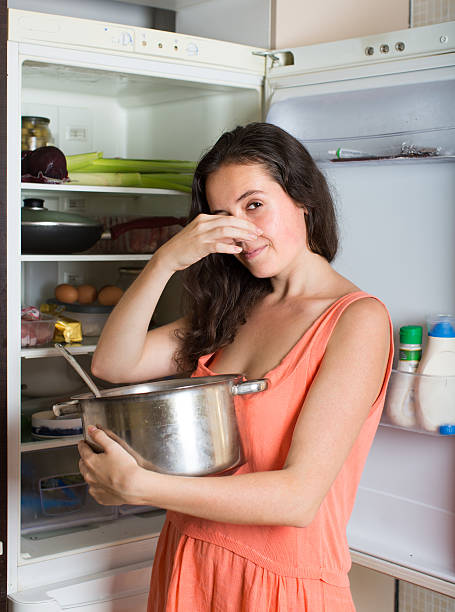 Girl holding her nose because of bad smell Girl holding her nose because of bad smell from food near refrigerator  at home addle stock pictures, royalty-free photos & images