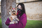Girl with protective face mask for Covid-19, holding her puppy YorkShire Terrier in a public park.
