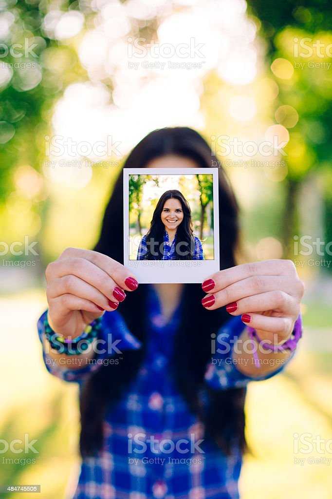 Girl holding instant photo stock photo