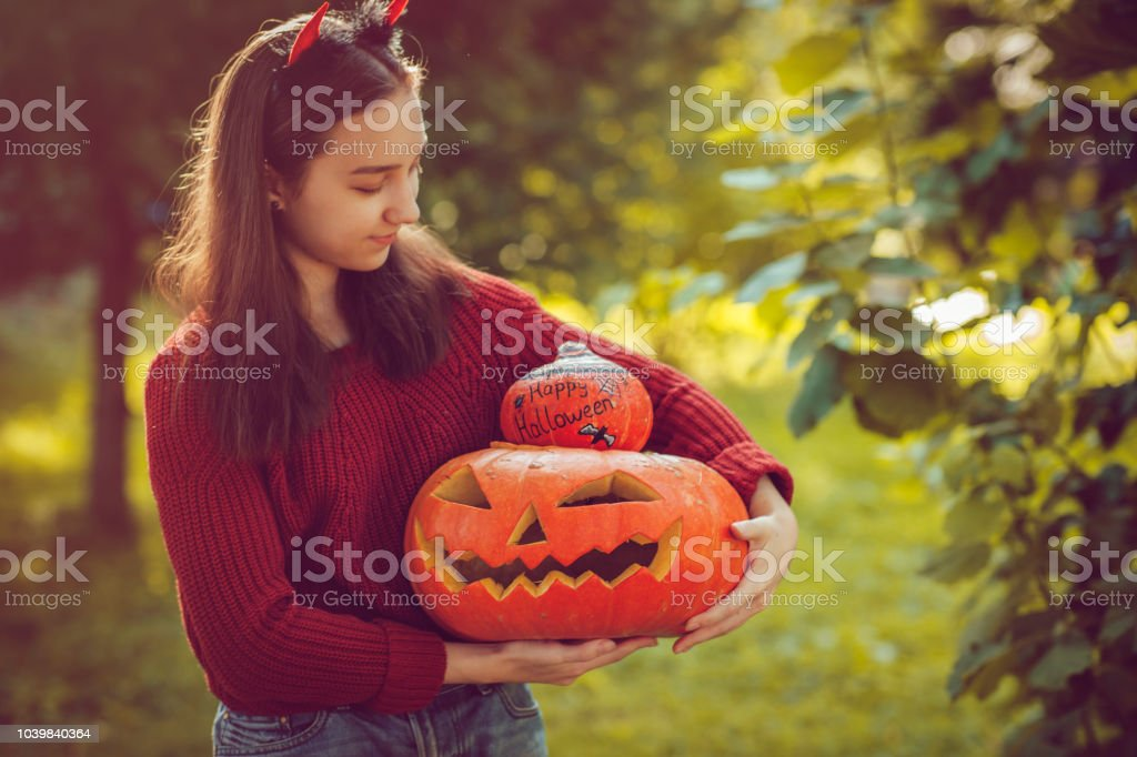 Girl holding jack o' lantern and painted pumpkin stock photo