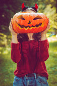 Girl with pumpkins at Halloween in autumn