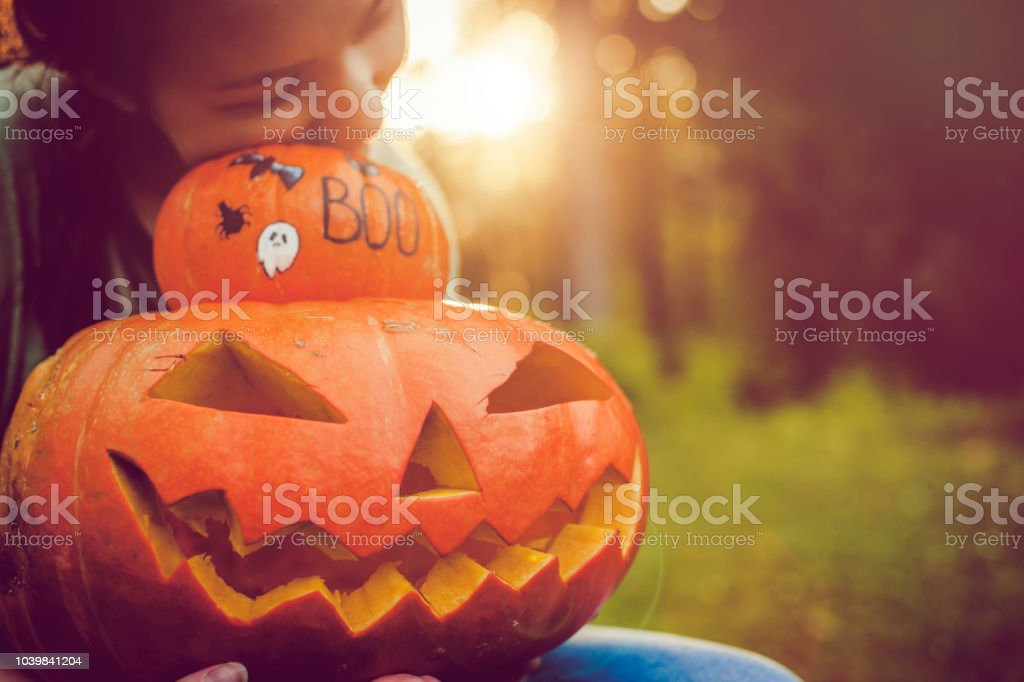 Girl holding jack o' lantern and pumpkin stock photo
