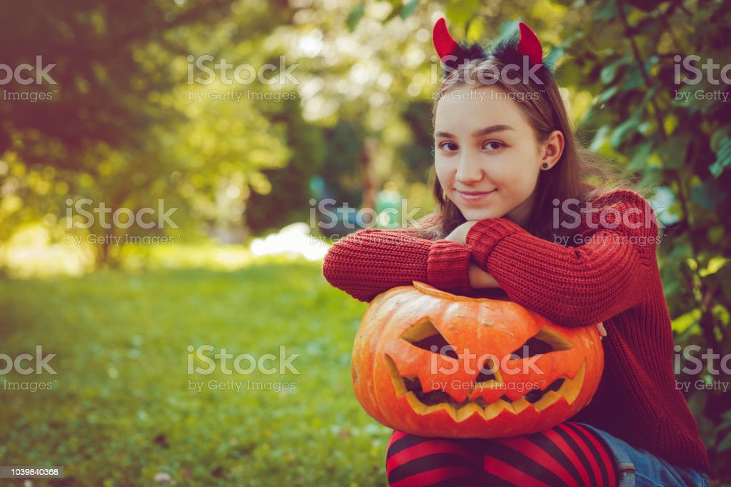 Girl holding jack o' lantern Halloween pumpkin stock photo